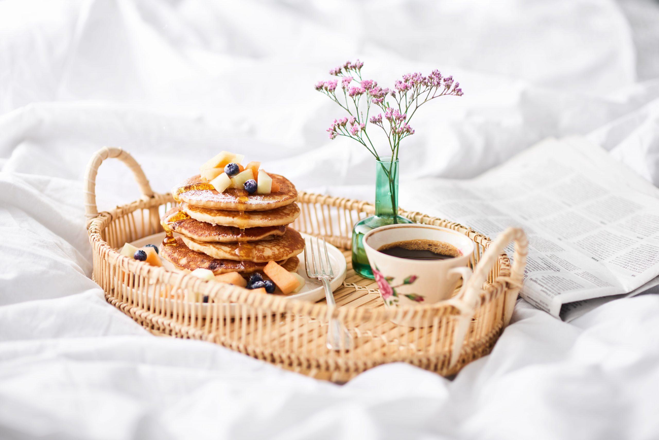En hög med pannkakor vackert uppdukat i en korg på sängen.