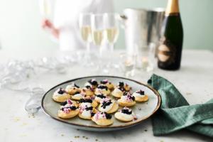 Kaviarpuffar på ett fat med champagneglas i bakgrunden. Festkänsla.