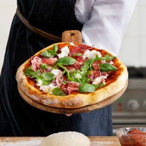 En kock håller en härlig nybakad pizza på en bricka i handen