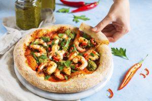 En rund pizza med jätteräkor. En hand tar en bit av den goda pizzan.
